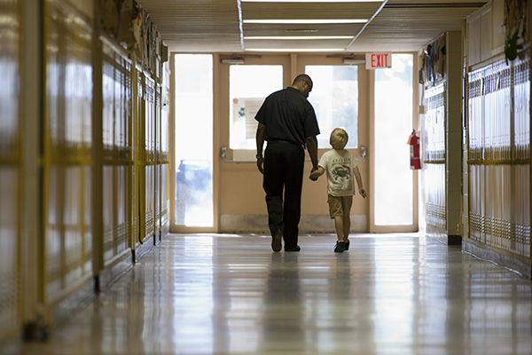 Teacher with student walking in school hall