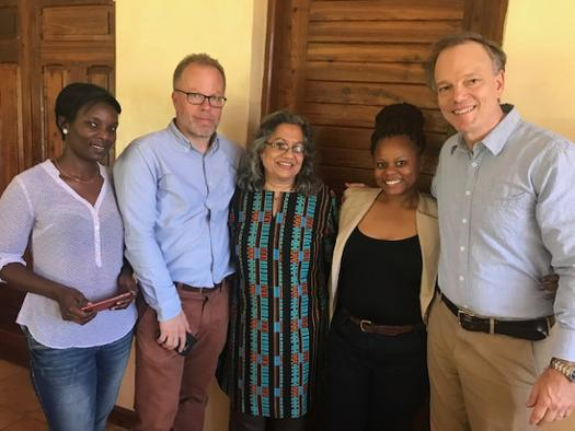 Paul (far right) and Anu (center) with EDI staff at their office in Dar es Salaam.