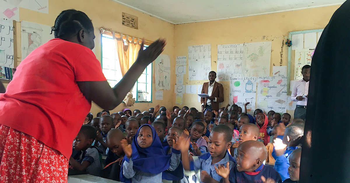 A teacher stands in front of a classroom of children