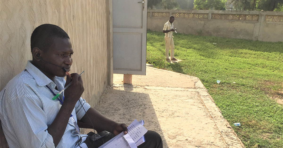 A telephone interviewer in Senegal finds a quiet outdoor space for surveying.