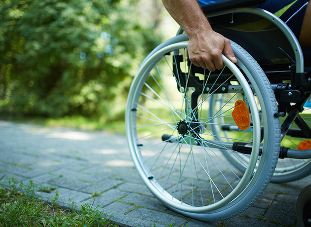 close up of male hand on wheelchair wheel