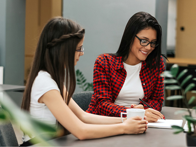 Two female business entrepreneurs working together in an office