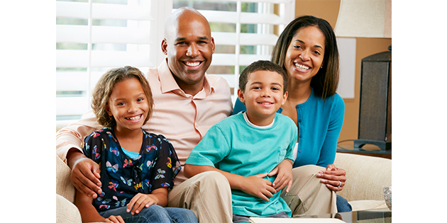 Smiling family sitting on a couch together building strong families