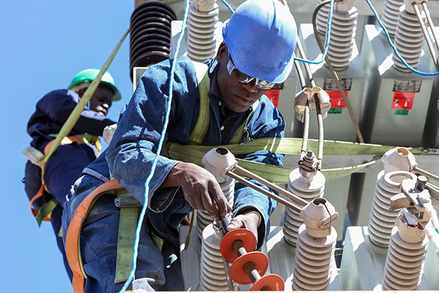 Electricians in Africa working on high voltage power lines