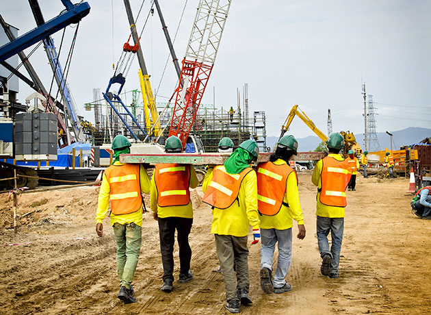 construction workers carrying beams