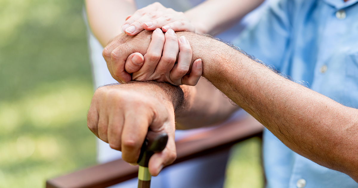 Caring nurse helping senior man sitting on bench in gaden. Asian woman, caucasian man. Holding hands with cane, close up.