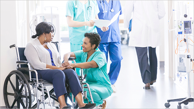 Nurse assisting woman in wheelchair