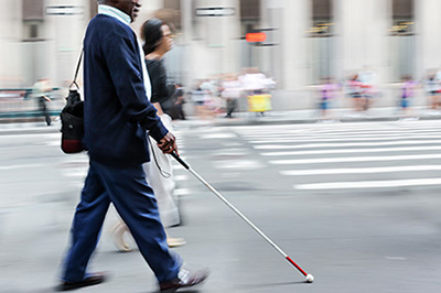 A disabled person walks on a city street.